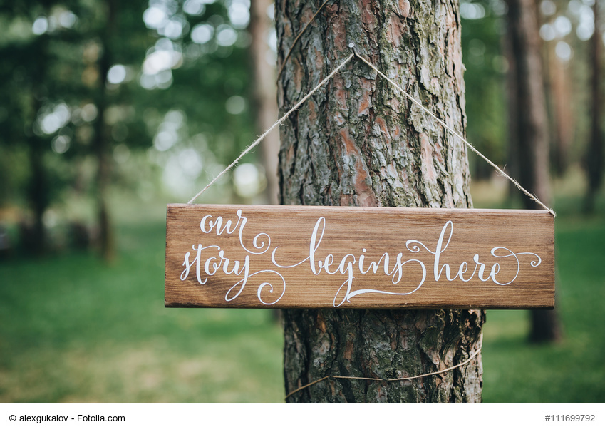 a wooden plaque with the inscription hanging on the tree in a pine forest