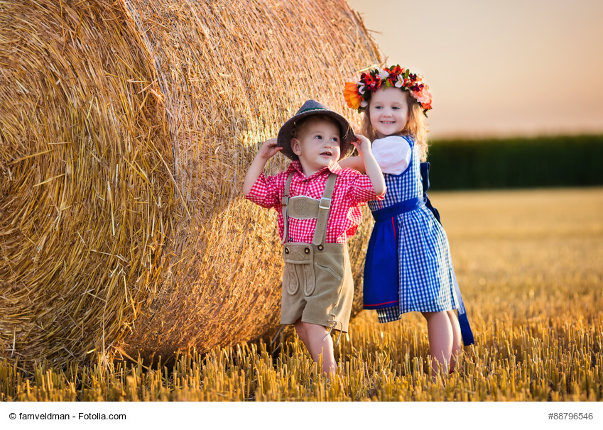 Kids in traditional Bavarian costumes in wheat field. German children eating bread and pretzel during Oktoberfest in Munich. Brother and sister play at hay bales during autumn harvest time in Germany
