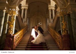 Ein glückliches Brautpaar auf steigt die Treppe zur Hochzeit hinauf - Bild: denisfilm - fotolia.com