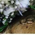 fedi-nuziali-e-bouquet-appoggiati-su-tavolo-legno-rustico-fotografia76