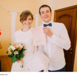 Happy stylish blonde bride and handsome groom holding marriage certificate