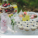 decorated sweet table for summer wedding picnic with sweets, cup