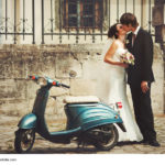 Goom kisses a bride standing behind a blue scooter