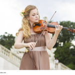 Beautiful smiling girl playing on the violin outdoors. Musician for the wedding.Violin under the open sky
