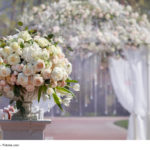 Big beautiful bouquet of roses in a vase on a background of a wedding arch. Beautiful set up for the wedding ceremony.