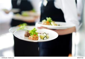 Waiter carrying plates with meat dish © MNStudio